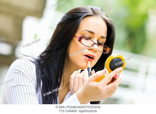 Applying lips make-up on the street young woman