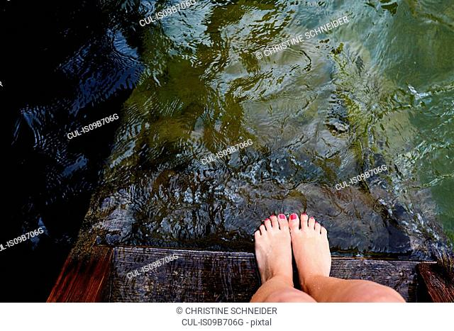 Woman's feet at edge of wooden pier by water