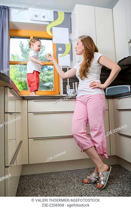 woman with a 1, 5 years old boy in the kitchen