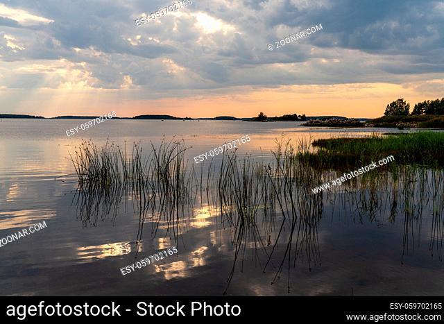 A colorful sunset and expressive sky reflections in a calm and peaceful lake with reeds in the foreground