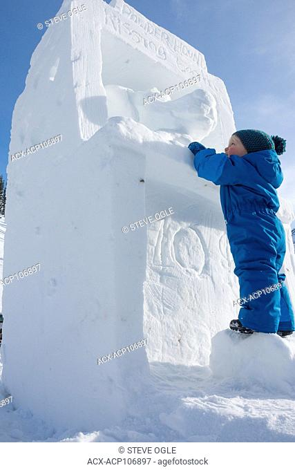 A toddler checks out a snow sculpture depicting a kissing booth for ten cents