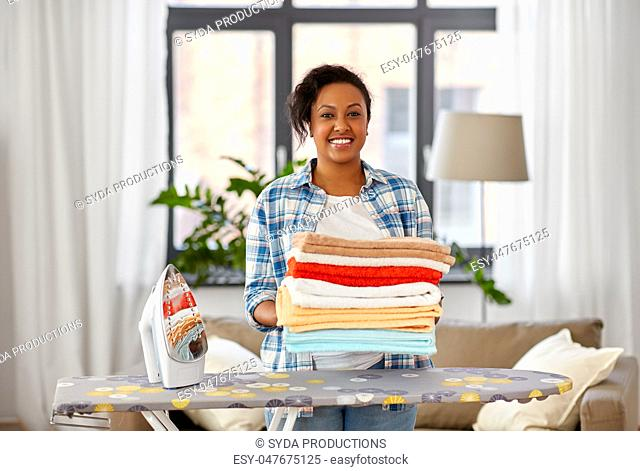 african american woman with ironed linen at home