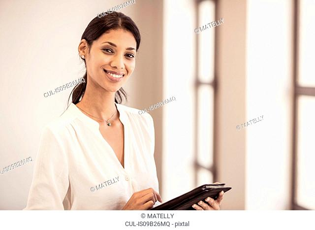 Portrait of young businesswoman using digital tablet in office