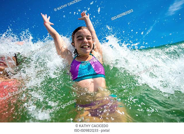 Girls jumping with joy in ocean wave