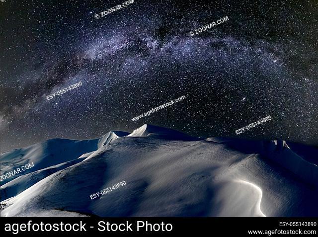 Night winter snow-covered mountain ridge in Moon light pastel illumination and starry Milky Way in sky (Ukraine, Carpathian Mountains, Svydovets Range