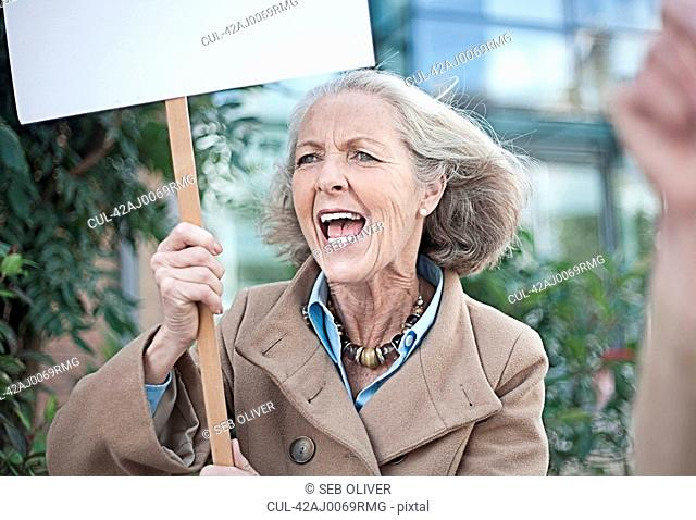 Older woman carrying protest sign