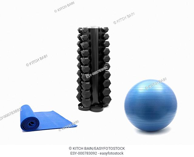 A fitball, exercise mat and a dumbell rack isolated against a white background
