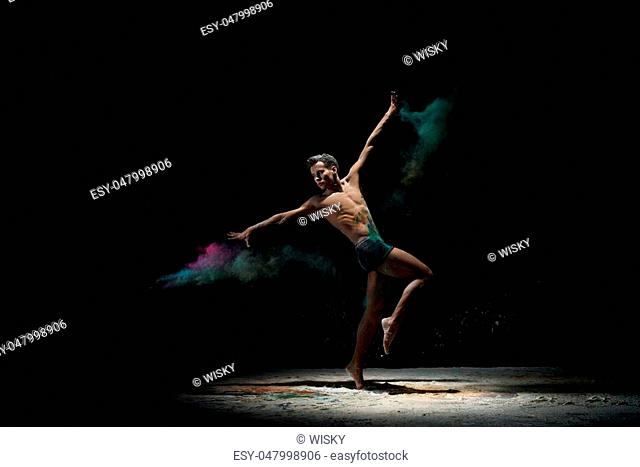 Modern art performance - young flexiblenaked dancer performing on dark stage in cloud of white colorful paints, in motion