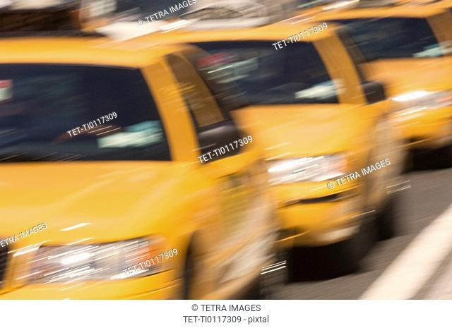 Three taxi cabs on street in New York NY