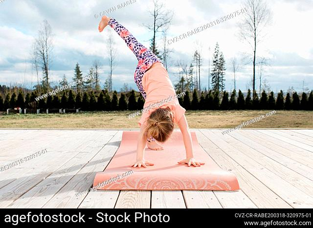 young girl stretching doing yoga in her back yard at home