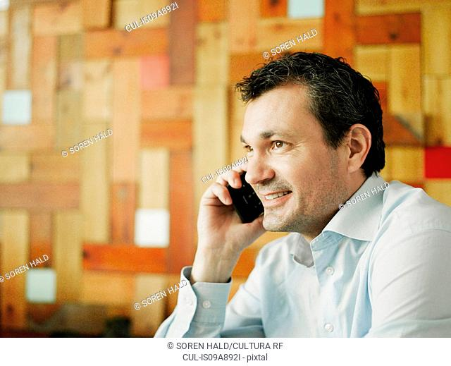 Mature man using cellphone, smiling