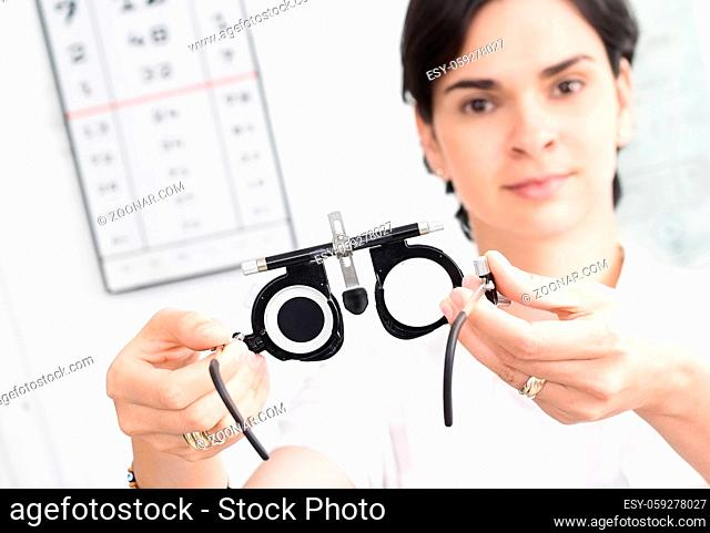 Young female optometrist with an universal messbrille in hand