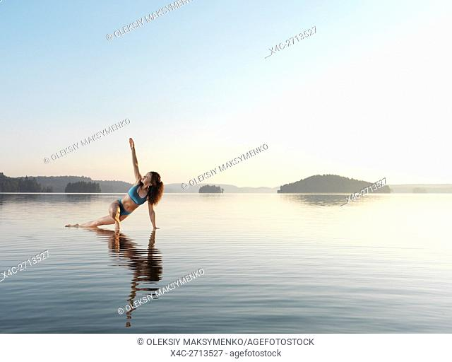 Young woman practicing Hatha yoga on a floating platform in water on the lake in early morning. Yoga, a variation of Triangle pose, Trikonasana