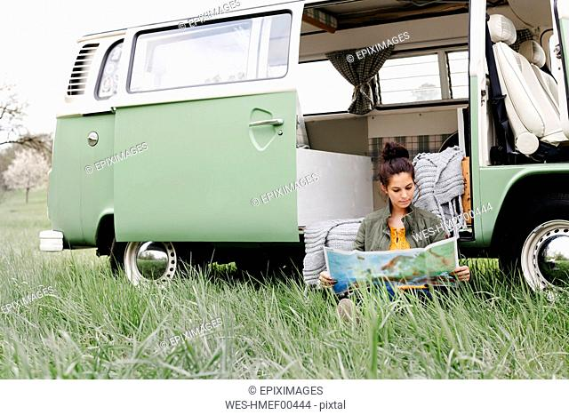 Young woman studying map, sitting in the grass, in front of her camper