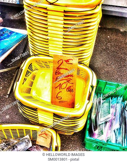 Stack of yellow baskets for sale in flea market, Clermont Ferrand, Auvergne, France, Europe