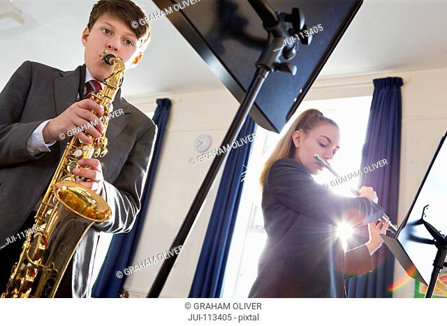 Middle school students playing flute and saxophone in music class