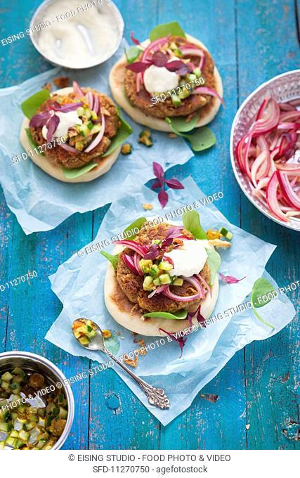 Chickpea burgers on unleavened bread with red onions, vegetables and a yoghurt sauce