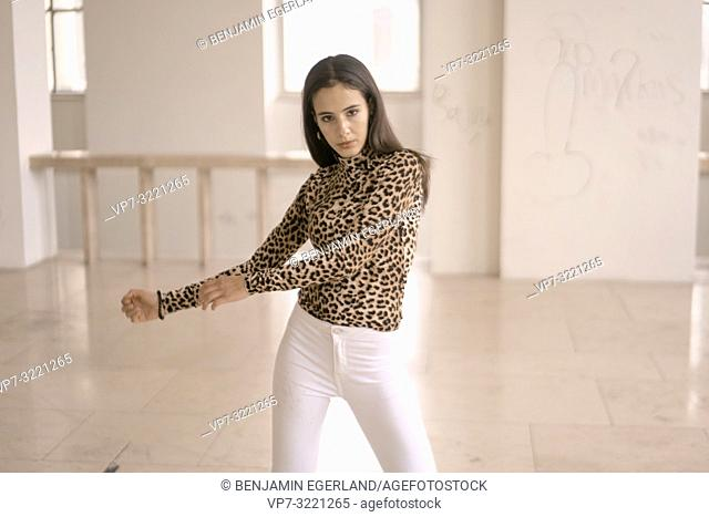 confident woman dancing indoors, fashionable clothing style, movement, in Munich, Germany