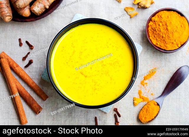 Turmeric drink, latte, tea, milk with cinnamon with fresh and dried turmeric on a textile grey background. Top view