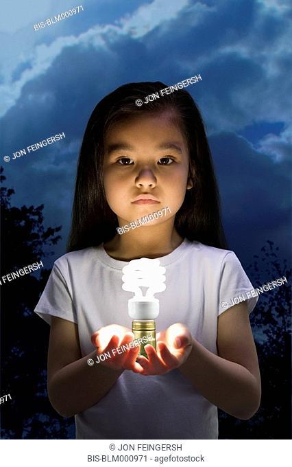 Chinese girl holding glowing cfl lightbulb