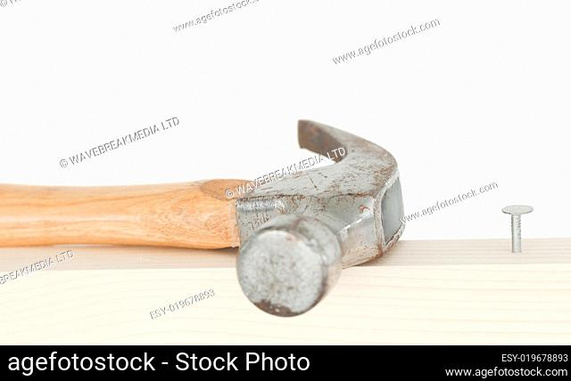 A hammer and a drived nail on a wooden board