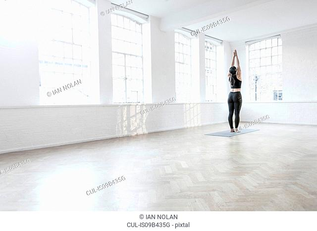 Rear view of woman in dance studio stretching