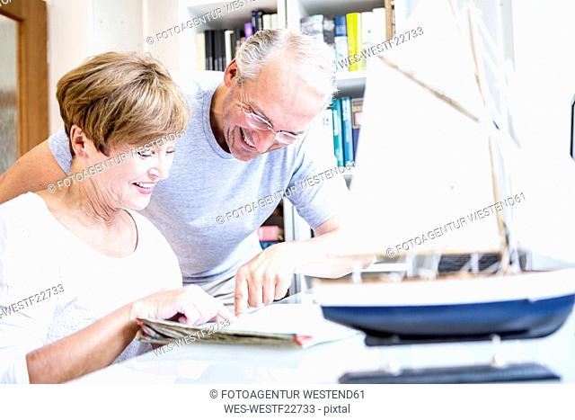 Senior couple at desk with magazine and model ship