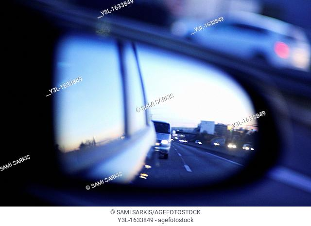 Traffic on highway reflected by side-view mirror at dusk, blurred motion