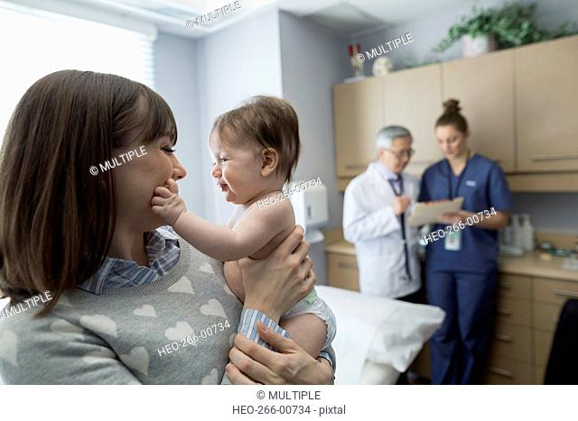 Mother holding baby in pediatrician examination room