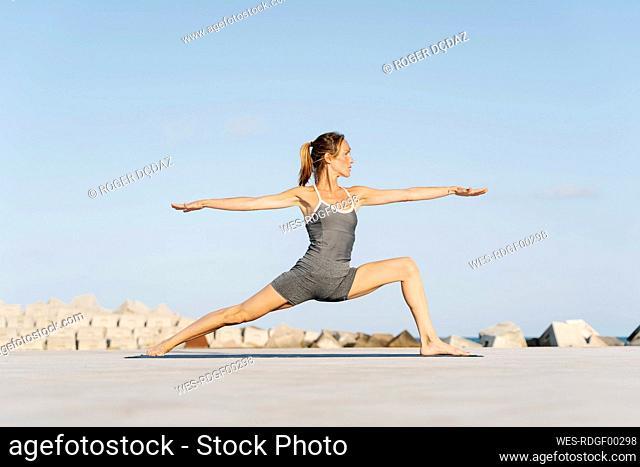 Female sportsperson doing warrior position on exercise mat