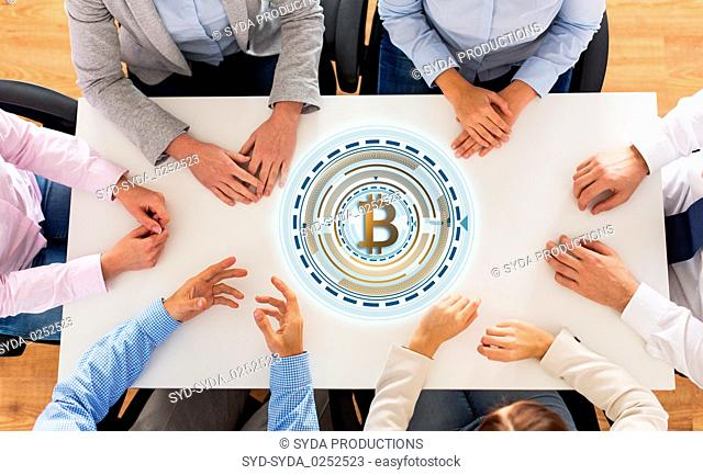 business team at table with bitcoin icon