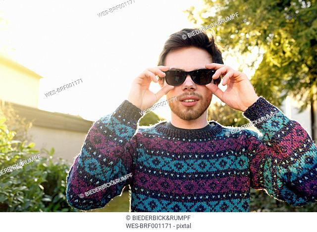 Portrait of young hipster wearing sunglasses and knit pullover
