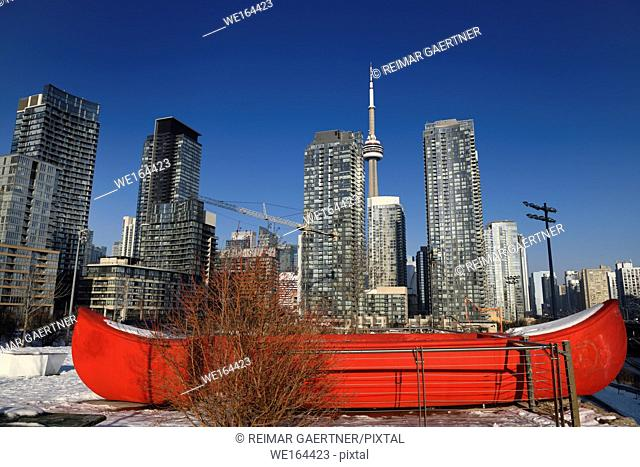 Red canoe in Canoe Landing Park in downtown Toronto with highrise condos and CN tower