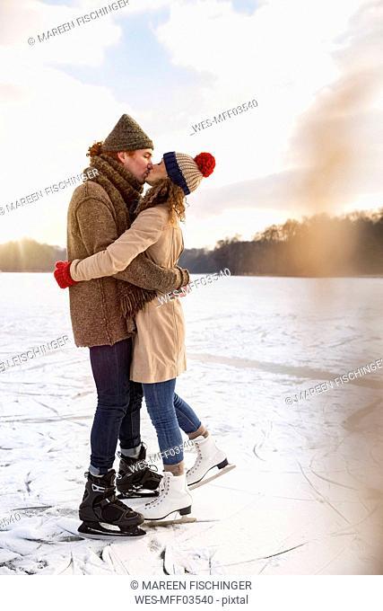 Couple with ice skates kissing on frozen lake