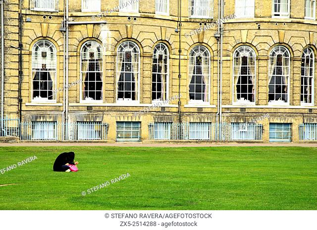 Woman sitting on the grass in front of the De Vere University Arms Hotel - Cambridge, England