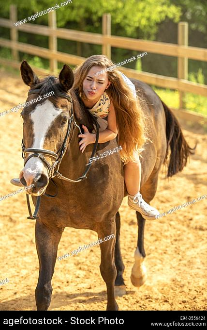 A 14 year old brunette girl riding her horse