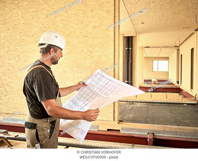 Worker with helmet holding construction plan