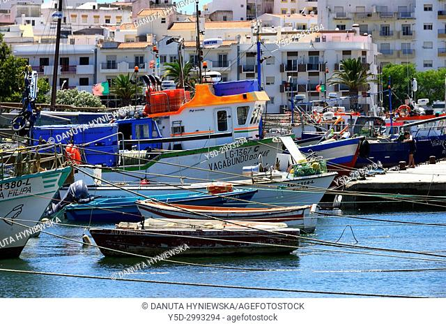 Traditional fishing boats moored in the harbour, in background old town, Lagos, Algarve, Portugal, Europe