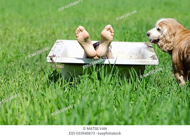 Woman lying down in a bathtub on the green grass and a dog watching