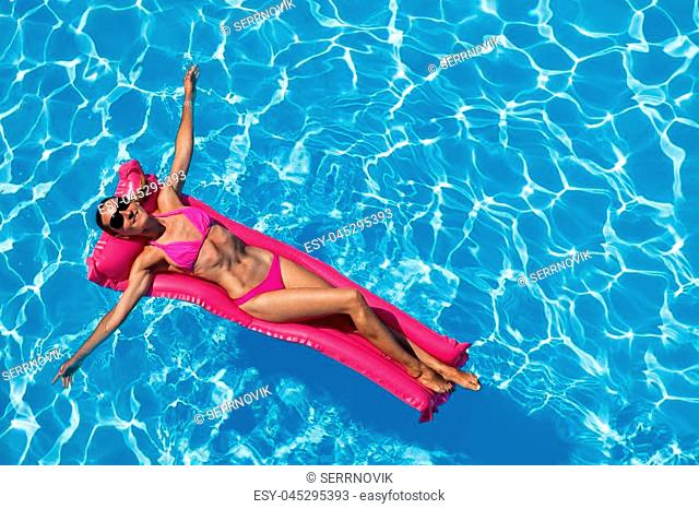 Top view of slim young woman in sunglasses relaxing on the pink air mattress in the swimming pool