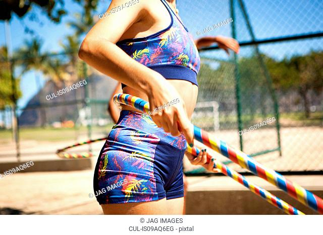 Young woman with hula hoop around waist, outdoors