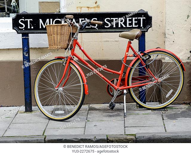 Red woman's bicycle parked by St Michael's Street road sign, Oxford, England, UK
