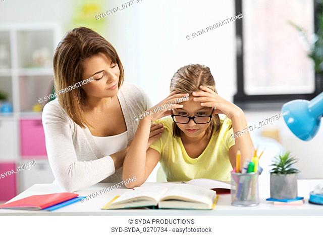 mother helping daughter with difficult homework
