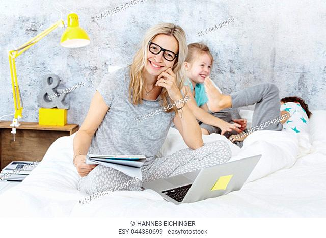 Happy business mum at work while her kids are playing in bed and having fun