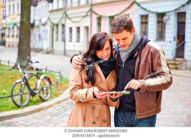 Paar in einer fremden Stadt sucht nach dem Weg mit einem Tablet Computer