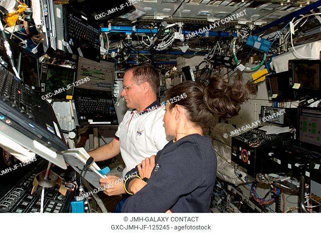 NASA astronauts Kevin Ford, STS-128 pilot; and Nicole Stott, Expedition 20 flight engineer, work in the Destiny laboratory of the International Space Station...
