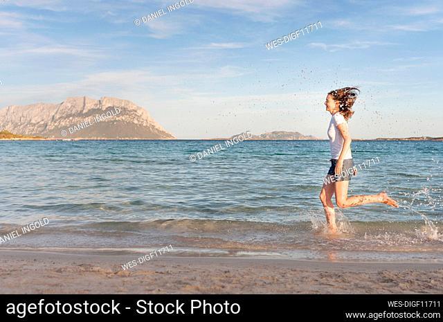 Happy woman running at seashore splashing with water, Sardinia, Italy