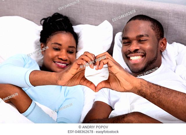 Happy African Couple Lying On Bed Making Heart Shape