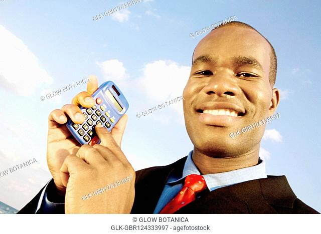Portrait of a businessman holding a calculator and smiling