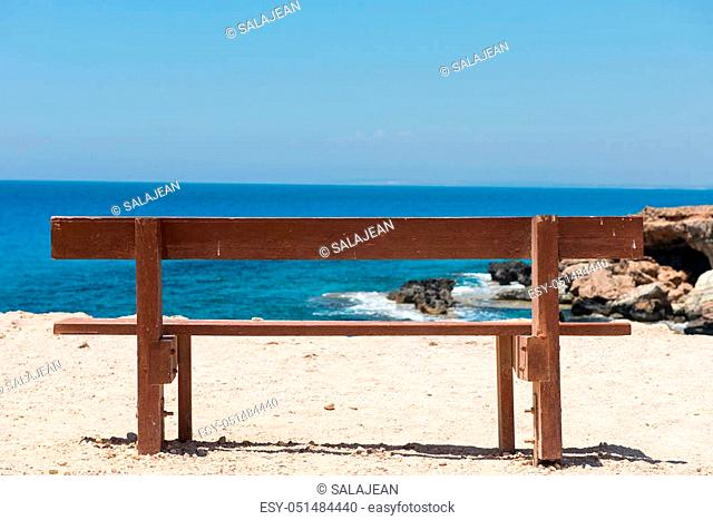 Wooden empty bench with a majestic sea view. Blue sea water in the background